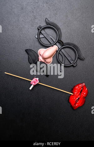 Moustache and a red mouth on wooden sticks on black background , copy space, as the male and female concep - Stock Photo