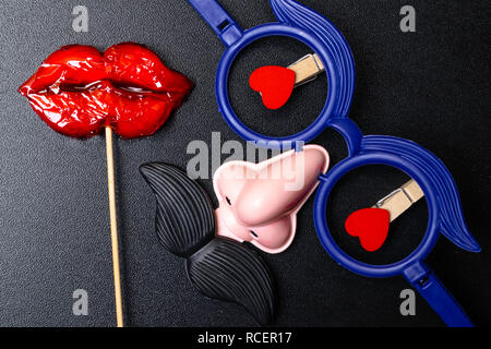 Moustache and a red mouth on wooden sticks on black background (copy space for your text) as the male and female concept, men and women - Stock Photo