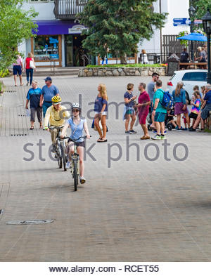 Woman and man riding bicycles on Willow Bridge Road, Vail, Eagle County, Colorado, USA - Stock Photo