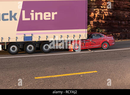Two cars accident. Crashed cars. A red coupé/sedan against the back of a big truck. Big damage. On the road with environment background. - Stock Photo