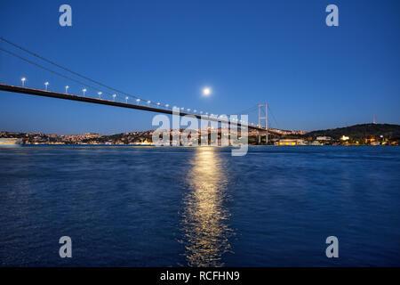 Bosphorus Bridge on background of night coast under bright moon - Stock Photo