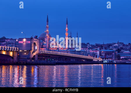 Galata Bridge and Yeni Cami Mosque in Istanbul at night - Stock Photo