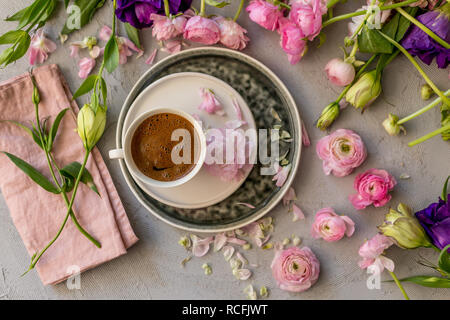 Upper view shot of a cup of coffee in the middle of floral frame of pink ranunculus and purple and yellow lisianthus - Stock Photo