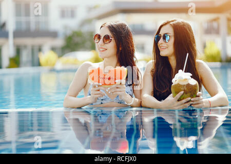 two girls having fruit by the pool - Stock Photo