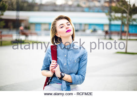 Walking cute girl with short flying blond hair and bright pink lips holding her marsala backpack on the shoulder and wearing blue denim shirt and grey tulle skirt. - Stock Photo