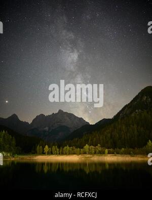View of the Milky Way over Jasna Lake and the Julian Alps, near Kranjska Gora, Gorenjska, Slovenia - Stock Photo