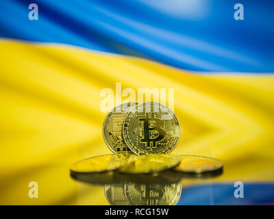 Bitcoin gold coin and defocused flag of Ukraine background. Virtual cryptocurrency concept. - Stock Photo