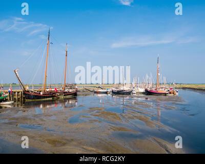 Sailing boats in marina at low tide, West Frisian island Schiermonnikoog, Netherlands - Stock Photo