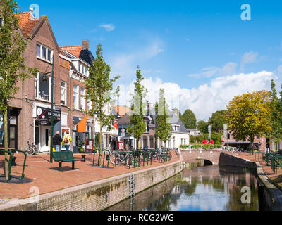 People walking on quayside with shops and canal in old town of Dokkum, Friesland, Netherlands - Stock Photo