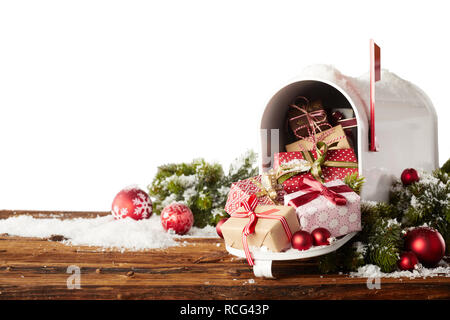 Colorful gift-wrapped Christmas presents and red baubles spilling from a letterbox onto a rustic wooden table with snow and copy space - Stock Photo
