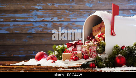 Mailbox overflowing with Christmas presents and colorful red baubles on a rustic wood background with copy space in banner format - Stock Photo