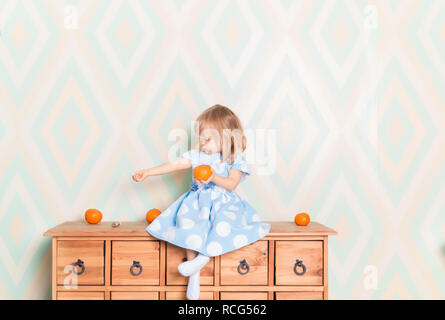 Portrait of blonde Caucasian baby girl with blue eyes in elegant dress and white socks sitting on wooden dresser with tangerine clementine fruit in hand and looking sideways at her hand. Amazement - Stock Photo