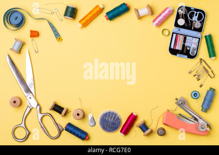Composition with threads and sewing accessories - scissors, centimeter, pins on yellow background.