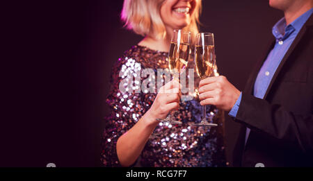 Photo of happy couple with champagne glasses with champagne on black background - Stock Photo