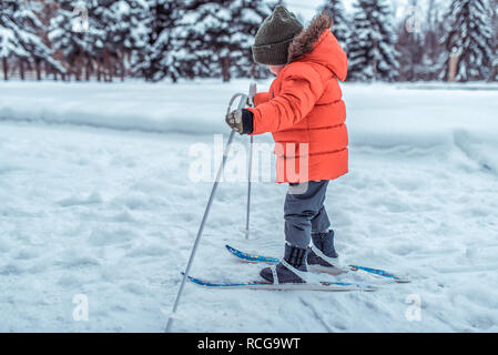 A small child of 3-5 years old, a boy in winter on children's skis, in a warm jacket and hat. Rides toy skiing. The first steps in an active lifestyle in a snowy forest. - Stock Photo