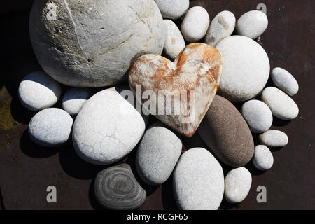 White painted weathered wooden heart grouped with beach pebbles as garden decoration. - Stock Photo