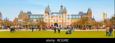 Amsterdam, Netherlands - March 31, 2016: Panoramic banner background with people, grass field and view of Rijksmuseum, Museumplein - Stock Photo