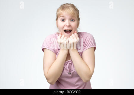 Young woman smiling very happy surprised holding hands near head being amazed on white background. - Stock Photo