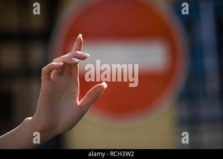 Close-up of female hand on blurred Do Not Enter road sign background - Stock Photo