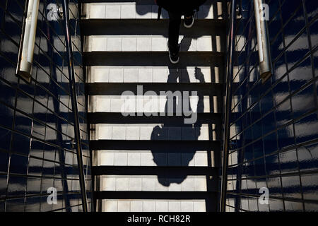 Top down shot of the shadow of a man walking down the stairs into the metro in Toronto city centre - Stock Photo