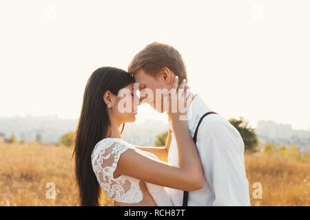 Loving couple dressed in white, ready to kiss outdoors with closed eyes, touching, gentle each other with a blurred landscape in background, golden gr - Stock Photo