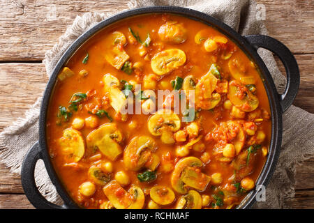 Vegan Indian Mushroom Curry with Spinach, Tomatoes and Chickpeas closeup in a frying pan. horizontal top view from above - Stock Photo
