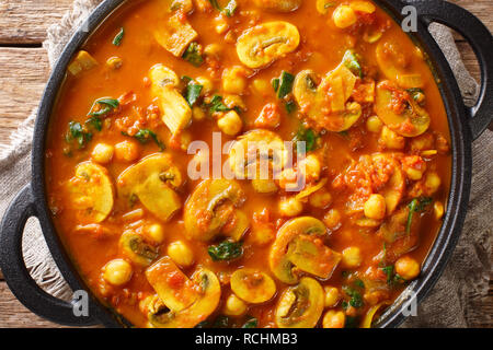 Freshly cooked mushroom curry with spinach, tomatoes and chickpeas close-up in a frying pan. horizontal top view from above - Stock Photo