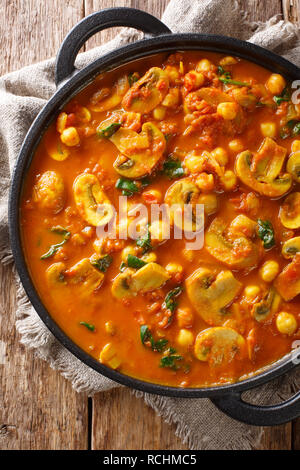 Vegan Indian Mushroom Curry with Spinach, Tomatoes and Chickpeas closeup in a frying pan. Vertical top view from above - Stock Photo