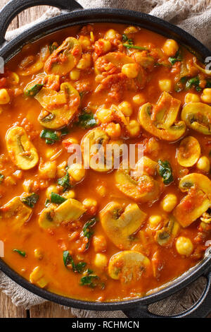 Freshly cooked mushroom curry with spinach, tomatoes and chickpeas close-up in a frying pan. Vertical top view from above - Stock Photo