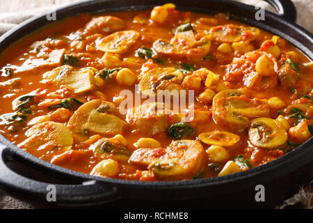 Hot Asian mushroom curry with spinach and chickpeas close-up in a frying pan. horizontal - Stock Photo