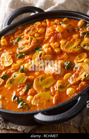 Mushroom curry with spinach and chickpeas close-up in a frying pan on the table. vertical - Stock Photo