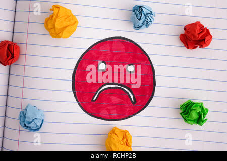 Sad face with colorful crumpled paper balls on notebook sheet. Close up. - Stock Photo