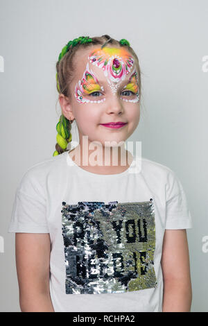Beautiful little girl with a painted face with flowers. face painting - Stock Photo