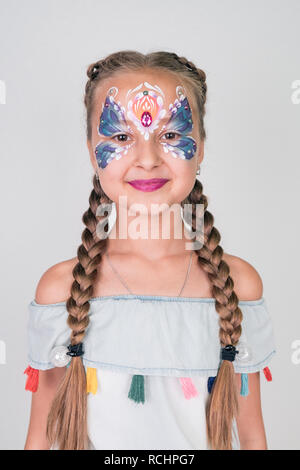 Charming girl with a blue butterfly painted on her face, on white background. face painting - Stock Photo