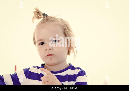Boy child with blond hair ponytail in sailor shirt on sunny summer day outdoors. Nautical fashion, vacation style concept. - Stock Photo