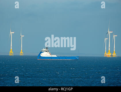 Aberdeen bay wind farm operational from May 2018 flanks the oil supply vessel NAO Prosper at anchor. - Stock Photo