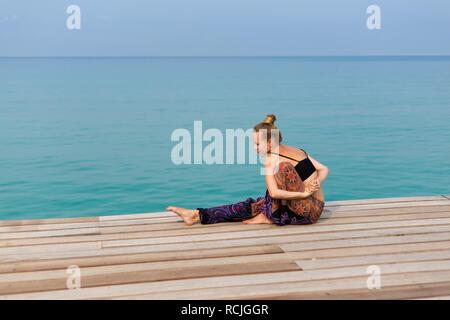 Summer yoga session on beautiful wooden pier, Bang Bao beach - tropical koh Kood island in Thailand. - Stock Photo