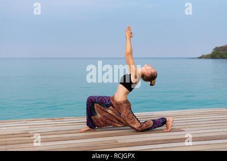 Summer yoga session on beautiful wooden pier, Bang Bao beach - tropical koh Kood island in Thailand. Warrior pose - Virabhadrasana - Stock Photo