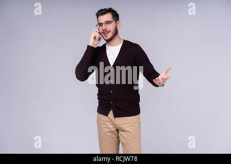 Image of happy young bearded emotional man standing over white wall background isolated. Looking aside while talking by phone. - Stock Photo