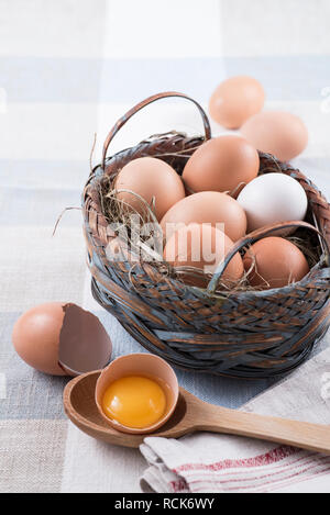 Fresh brown and white eggs in basket on table cloth - Stock Photo