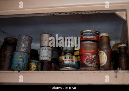 Old tins of food in cupboard in kitchen in derelict 1930s deco style house, Rayners Lane, Middlesex UK - Stock Photo
