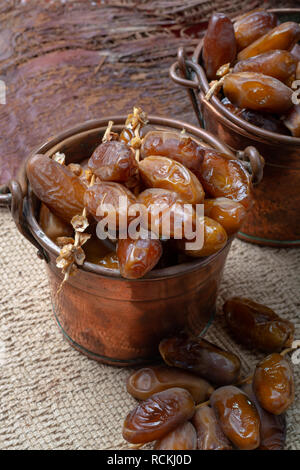 Authentic Tunisian Deglet Nour dried dates with soft honey-like taste in copper buckets - Stock Photo