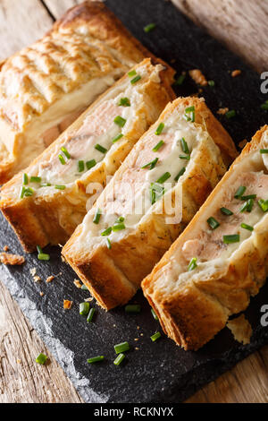 Baked salmon pie with cheese close-up on the table. vertical - Stock Photo