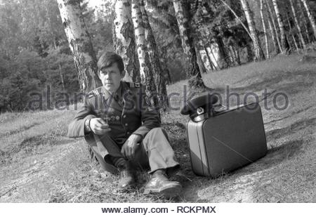 The soviet soldier in uniform sits in the forest and smokes. This is my friend. In summer of 1986 he came on vocation from Soviet Army. I met him by the road to his house in the forest and taken some photos. - Stock Photo