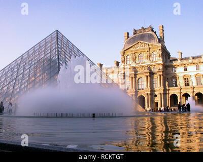 Pyramid and ornamental fountain in the Cour Napoléon, Palais du Louvre, Paris, France - Stock Photo