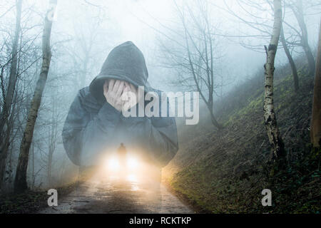 A double exposure of a hooded figure holding his face in his hands with a figure silhouetted by car headlights in a foggy, winter forest. With a grain - Stock Photo