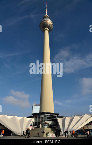 Berlin, Germany - November 10, 2018. Soaring shaft and silver sphere of Fernsehturm TV tower in Berlin, with Body Worlds (Menschen Museum) and people. - Stock Photo