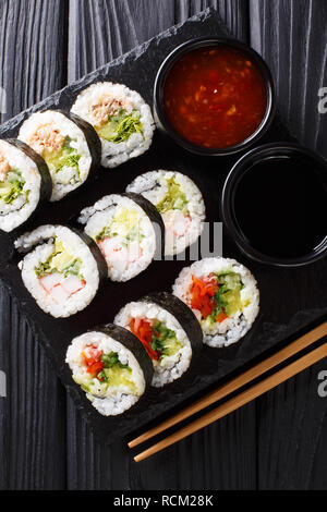 Futomaki rolls with various fillings are served with sauces close-up on a slate board on the table. Vertical top view from above