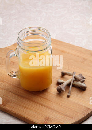 freshly made chicken bone broth in glass jar with bones nearby - Stock Photo