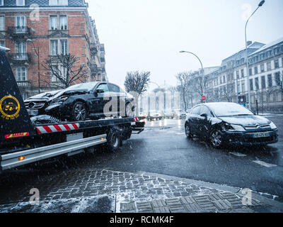 STRASBOURG, FRANCE - MAR 2, 2018: Car accident on French street between luxury limousine Mercedes-Benz and Citroen car on a snowy tempest cold day traffic jam tow truck  - Stock Photo